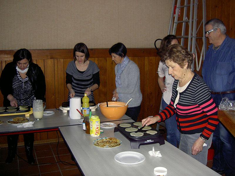 Pendant le spectacle, les bénévoles préparent les crèpes pour le goûter